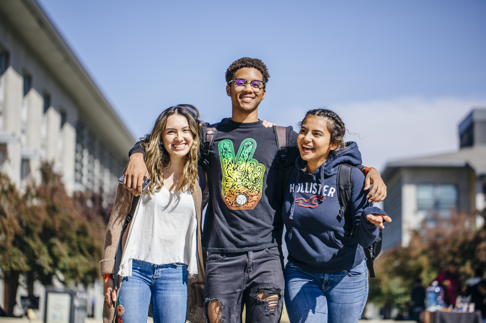 Three students of color stroll along Scholars Lane at UC Merced.